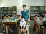 Cik. Lee sedang memeriksa hasil kerja murid.
